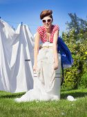 Pin up style photo of woman doing laundry using vintage wringer washing machine