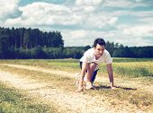 Young determined athletic man in the start position, ready to run on a path in a rural area, with gr