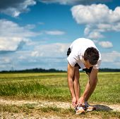 Sportsman on a rural track in open countryside bending over tying his laces on his running shoes bef