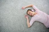 Blond girl relaxing on carpet floor with headphones on