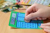 Coquitlam BC Canada - June 15, 2014 : Woman scratching lottery ticket called Bingo. It's published by BC Lottery Corporation has provided government sanctioned lottery games.
