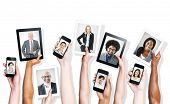 Hands Holding Digital Devices with Business People's Images