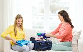 travel, vacation and friendship concept - two smiling teenage girls packing suitcase at home