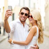 summer holidays, technology, love, relationship and dating concept - smiling couple taking selfie wi