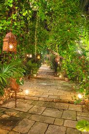 foto of luminaria  - Beautiful garden path at night scene illuminated by candles and lanterns - JPG