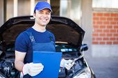 Smiling mechanic holding a clipboard in front of a car