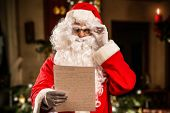 picture of letters to santa claus  - Santa Claus reading a letter - JPG