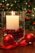 Christmas candle burning brightly in front of tree