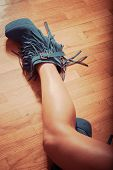 long slim woman legs in blue ankle high heel fringe boot indoor shot on parquet retro colors