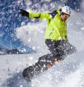 Snowboarder in high mountains during sunny day.