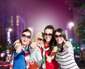 holidays, friendsip, nightlife and happy people concept - happy teenage girls or young women showing thumbs up over night city background
