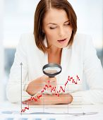 business, documents, statistics and people concept - businesswoman looking through magnifier to graphs in office