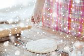 cooking and home concept - close up of female hand sprinkling dough with flour
