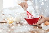 cooking, food, people and home concept - close up of man whipping eggs or cream with whisk in bowl
