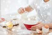 cooking, food, people and home concept - close up of man pouring milk to bowl