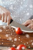 cooking, people, vegetarian food and home concept - close up of man chopping tomato on cutting board with big knife
