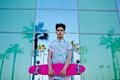 Stylish man in bright summer clothes standing with long-board
