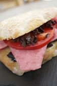Mortadella sandwich, tomato and black olives.