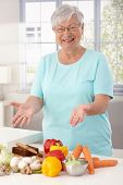 Happy grandmother showing healthy raw materials on kitchen counter, smiling, looking at camera.