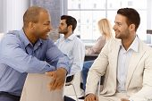 Businesspeople talking in office, smiling.