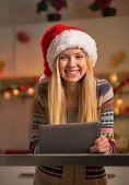 Portrait Of Happy Teenager Girl In Santa Hat Using Tablet Pc