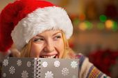 Portrait Of Smiling Teenager Girl In Santa Hat Hiding Behind Notepad