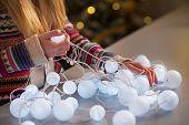 Closeup On Happy Teenager Girl In Santa Hat Untangling Christmas