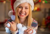 Portrait Of Happy Teenager Girl In Santa Hat Holding Tangled Chr
