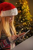 Profile Portrait Of Teenager Girl In Santa Hat Using Tablet Pc