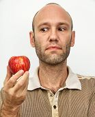 Man Questioningly Looking At Red Apple