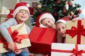Three little boys in Santa caps holding big giftboxes