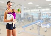 Young sporty girl with skipping rope and apple at gym club