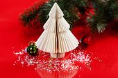 Christmas tree made of paper and decorations on red background