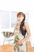 Young Pregnant Housewife Wearing Apron In The Kitchen Smiling