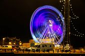 Ferris wheel at night in motion at the pier