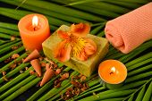 Spa set with towel, candle, soap ,orange orchid on palm leaf