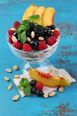 Healthy breakfast - yogurt with  fresh fruit, berries and muesli served in glass bowl on color wooden background