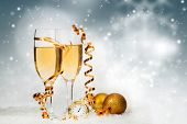 Glasses with champagne, clock close to midnight and Christmas balls on sparkling holiday background