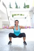 Beautiful hispanic sport woman doing squats with two pink dumbbell, outdoor.