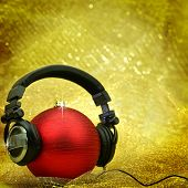 Christmas ball with headphones in glittering background