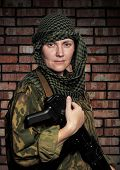 Portrait of the woman of the soldier with an automatic assault rifle
