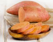 Raw Sweet Potatoes On A Wooden Table .
