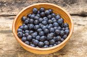 Ripe Blackthorn Berries In Clay Bowl On Wood Background