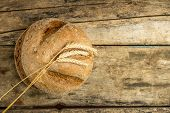 Loaf Of Whole Wheat Bread With Ears On Wood Background