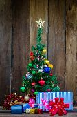 Christmas Tree With Colorful Ornaments A Wood Background