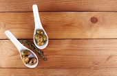 Green olives in oil with spices and rosemary in spoons on wooden table