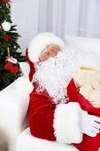 Santa Claus sleeping at home near Christmas tree