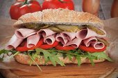 Submarine sandwich with baloney, pickles, tomato and rocket salad