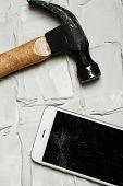 Broken iPhone with hammer on brick background