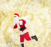 christmas, holidays and people concept - man in costume of santa claus running with bag over yellow lights background